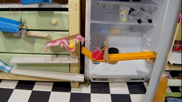 Een Rube Goldberg machine voert de kat als de baas van huis is